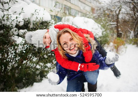Mother and the daughter cheerfully spend time in winter day. They walk in the snow-covered park. In hands at the woman snowballs. She in someone aims. Girl embraces mother. Both laugh. It is snowing.
