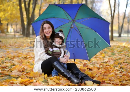 mother and the kid walk in the autumn park among gold foliage - stock photo
