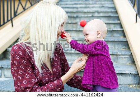 Mother and the little daughter with noses of clown sit in city park on steps - stock photo