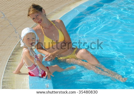 Mother and the little girl sit at pool