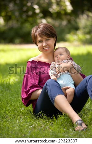 Mother and the small child sit in park on a lawn