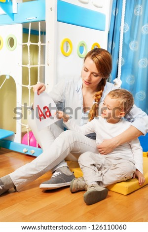 Mother and the son learning alphabet by showing slides with letters sitting in the corner of the room - stock photo
