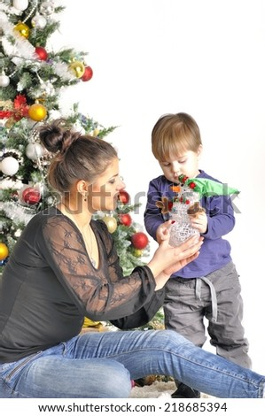 Mother and their small child sits near Christmas tree with toy - stock photo