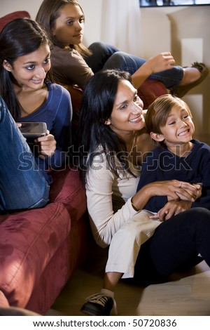 Mother and three children sitting together on living room sofa watching television - stock photo