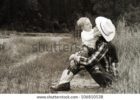 Mother and toddler boy playing in the field - stock photo
