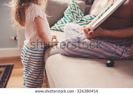 mother and toddler daughter reading book at home - stock photo