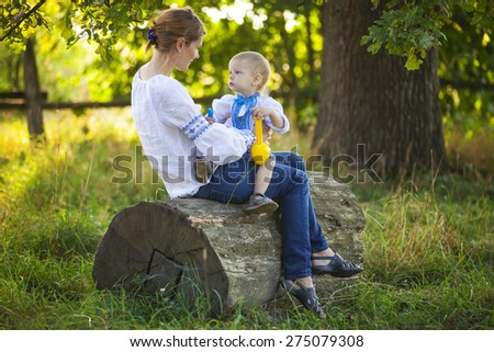 Mother and toddler son in Ukrainian style shirts playing outdoors - stock photo