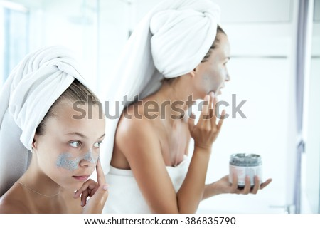 Mother and tween daughter make a clay facial mask, family skin care in the bathroom