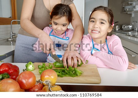 Mother and twin daughters learning to chop vegetables together in the kitchen, using a chopping board and surrounded by fruit and vegetables. - stock photo