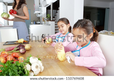 Mother and twin daughters learning to peel potatoes together in the kitchen, using a chopping board with fruit and vegetables.
