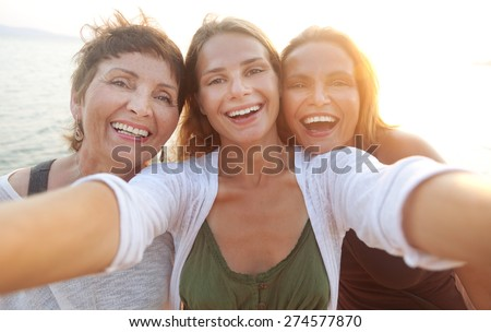 mother and two adult daughters are doing Selfe on the beach - stock photo