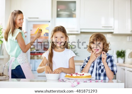 Mother and two children baking and tasting a fruit cake in the kitchen