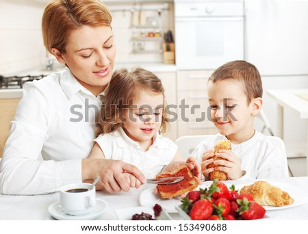 Mother and two children having breakfast together - stock photo