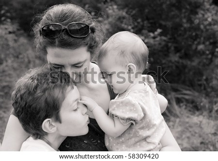 mother and two children in loving embrace, black and white