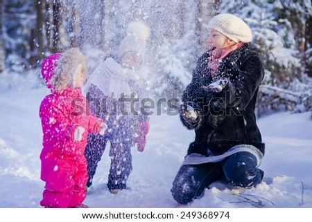 Mother and two children playing with snow in winter forest - stock photo