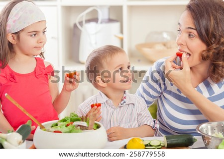 Mother and two children preparing and eating fresh vegetable salad - stock photo