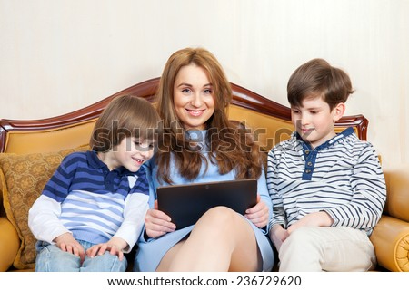mother and two children sitting on the sofa with a tablet computer - stock photo