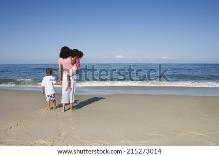 Mother and two children (5-7) standing on sandy beach, looking at Atlantic Ocean horizon, rear view