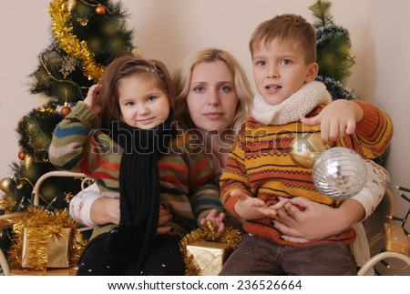 Mother and two children with golden balls over Christmas tree - stock photo
