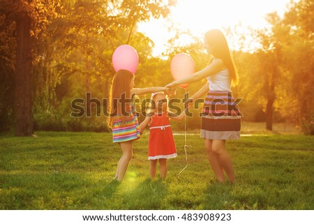 Mother and two daughters dance in a circle holding hands. Family time together. Cheerful picnic. Girls with balloons.
