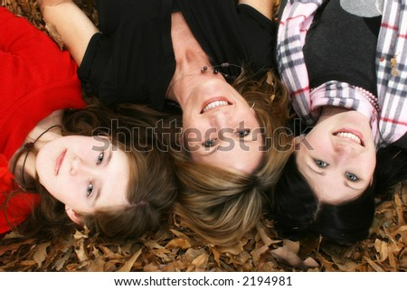 Mother and two daughters sitting in leaves.  Family portrait.