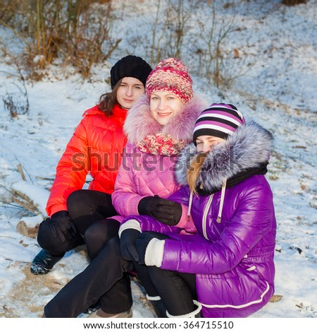 Mother and two daughters sitting on the bank of the river and dream outdoors in winter