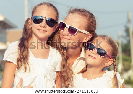 Mother and two daughters standing on the road at the day time. - stock photo