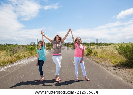 Mother and two daughters with arms raised