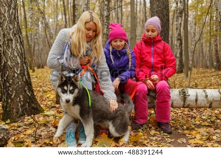 Mother and two daughters with dog breed husky sitting on fallen birch tree in woods