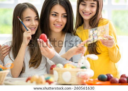 Mother  and two girls making Easter decoration in bright living room - stock photo