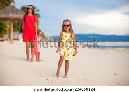 Mother and two her kids at exotic beach on sunset