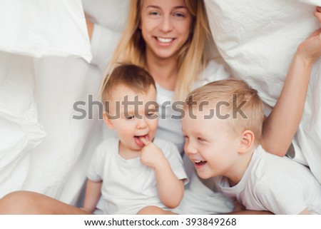 Mother and  two her sons playing and smiling in bed under a blanket. Happy family.