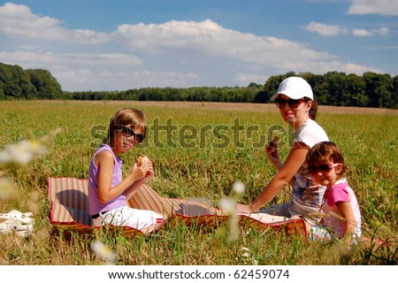 Mother and two kids having picnic outdoors - stock photo