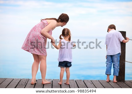 Mother and two kids  looking for fish from wooden dock - stock photo
