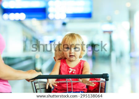 mother and two kids on luggage cart in the airport