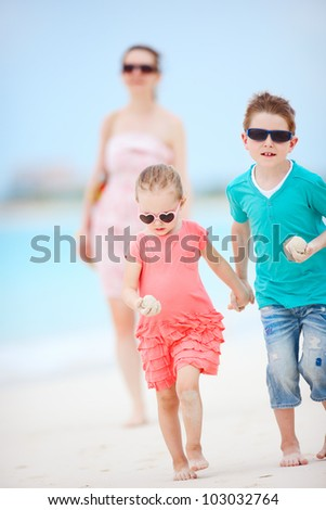 Mother and two kids running on tropical beach