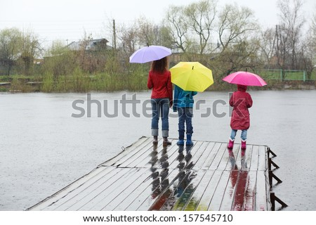 Mother and two kids standing by back at the pier in the rain - stock photo
