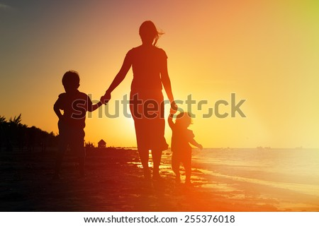 mother and two kids walking on sand beach at sunset - stock photo