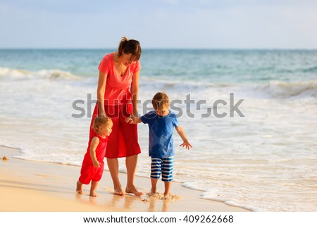 mother and two kids walking on the beach - stock photo