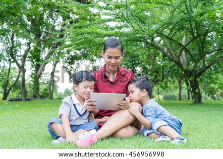 Mother and two little Brothers playing tablet PC in in the park. - stock photo
