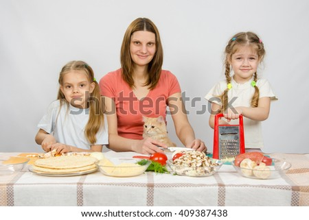 Mother and two little girls at a table prepared ingredients for the pizza. They were watching a cat - stock photo
