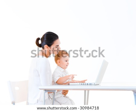 Mother and 2 years old baby boy sitting at the desk and using laptop computer. - stock photo