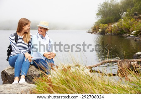 Mother and young adult daughter relaxing by a lake - stock photo
