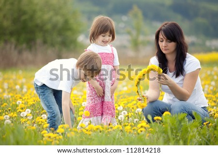 Mother and young children picking dandelion flowers  in a field. - stock photo