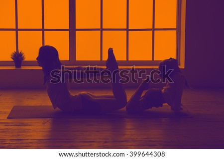 Mother and young daughter doing fitness yoga together. Silhouette fitness woman. Women silhouettes in the window sunset background. Orange violet toning image. Space for text. - stock photo