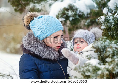 Mother and young daughter embracing in a winter park. Mother and daughter in her arms. Happy family. Childhood and parenthood happiness. They talk.