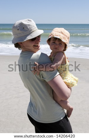 Mother and young daughter enjoying summer at the beach.