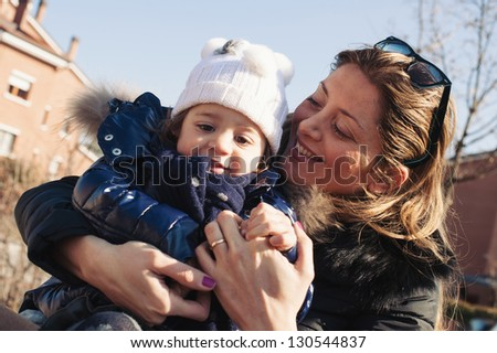 Mother and young daughter outdoors portrait In the park.