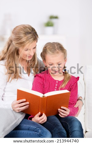 Mother and young daughter reading book on couch at home