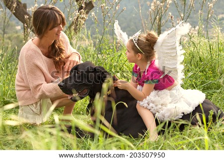 Mother and young daughter relaxing together with their pet dog in a lush green field on holiday during a sunny day. Animal pets, friendship and companionship. Active family caring for their dog. - stock photo